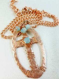 Hammered #copper metal #cross #pendant within an oval shape frame decorated with Swarovski Pacific Blue bicone crystals with copper wire wrapping. This pendant is suspended by an 18 inch link chain neckl