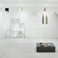 Thin beams double as garment rails at this minimal Tokyo concept store by Japanese studio Nendo.
