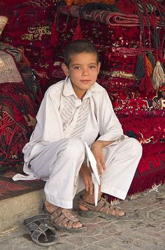 The carpet-seller's son, Mazar-e-Sharif, Afghanistan. Mazar-e-Sharif is the capital of Balkh province and is linked by highways with Kunduz in the east, Kabul in the southeast, Herat in the west and Uzbekistan in the north. (V)