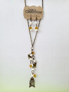 Juego de collar y aretes en #amarillo y #marfil. Con dijes de #mariposa y #jaula, color oro viejo. #jewellery #joyeria #handmade #hechoamano