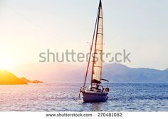 Beautiful racing yacht in the Mediterranean sea with blue sky and mountains on background, sailing boat at gold colorful sunset