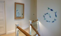 We worked with Jo Downs for bespoke glass..and created a shoal of fish swooping downstairs!