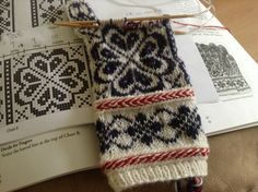 Norwegian Selbu Rose gloves, featuring a red and white Latvian braid.