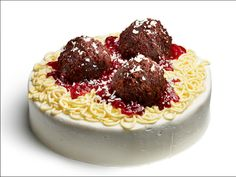 A fun Meatball and Spaghetti CAKE!  The base is a single layer chocolate cake. Cover with icing. Add some yellow food coloring to some white icing and pipe it thru a cookie press to make the 'spaghetti'. Take the second single layer of chocolate cake and shape it into three 'meatballs'. Lay them on top of the 'spaghetti'. Top all with a puree of strawberries for the sauce and sprinkle with shavings of white chocolate for the appearance of parmesan cheese!
