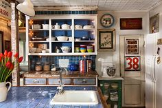 This hutch-like built-in was redone with paint, tile, and brackets that the homeowner-designer found at a flea market, already painted the perfect shade of blue