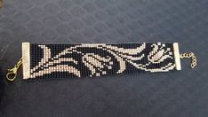 Black & gold bead loom bracelet with lilys