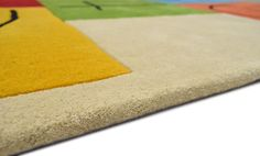 A fully Bespoke rug hand tufted with mixed New Zealand wool in black, taupe, turquoise, orange, green, red, yellow and purple. It has a pile depth of 10-12mm. Created using the customers own design. [side view] #CustomRugRoom