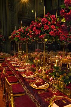 A long banquet table is decorated with a long mirrored runner and luxurious red velvet tablecloth.