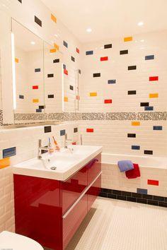 Dans la salle de bains des enfants, le carrelage métro blanc est incrusté de 4 coloris : des carreaux bleu, jaune, noir et rouge qui répondent à la couleur laquée du meuble vasques.