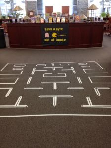 """Pac Man library display.  The sign reads """"Take a Byte out of books""""  The Ghost is ignorance.  The small yellow dots are covers of yellow books."""