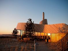 Restaurant Aan Zee situated in  Oosvoorne, Netherlands. Sustainable design includes a wind powered millstone. The building can be dismantled and reasembled elsewhere not altering the landscape