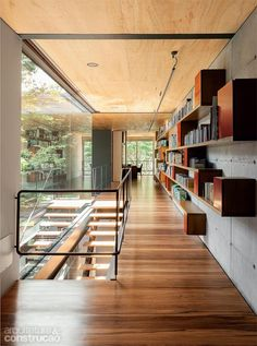 clean linear hallway punctuated by the staccato red storage boxes on the long shelves; polished wood floor + matte plywood ceiling + concrete wall + industrial baluster + glass wall to the side and end +light cantilevered stairs aros: Une maison de verre et de bois à Sao Paulo