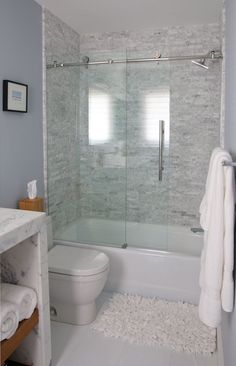 This traditional bathroom is clean and classy thanks to a frameless glass door and a light color scheme.