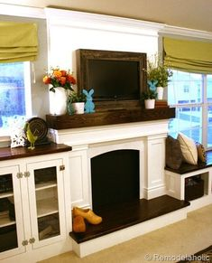 fake fireplace and mantle with a frame around the TV for basement. Books with plant stacked by lavonne
