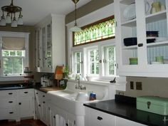 stain glass window above sink, drainboard sink with curved corners, cabinet sticks out a bit and shelf above sink