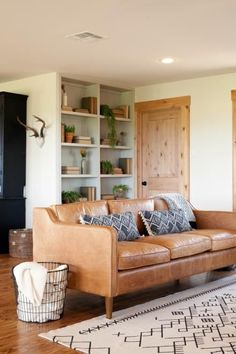 The renovated wooden floors and graphic carpet add to the brightness in the Zan family's newly remodeled living room, as seen on Fixer Upper.