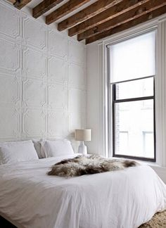 bedroom: white linen, timber beams, pressed metal wall and a lovely soft dead animal on the bed.