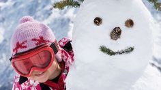 Girl peeking around snowman - Cultura Creative (RF/Alamy