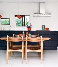 Love the black cabinets, warm wood and little Panton (?) pendant lights.