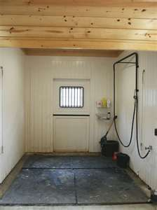 view of wash stall in one of our horse barns with finished floor and painted walls - Horse Stall Design Ideas