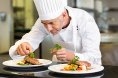 Closeup of a concentrated male chef garnishing food in the kitchen by Wavebreakmedia