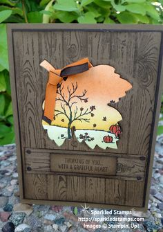 handmade Thanksgiving card from Sparkled Stamps  ... faux wooden gate/fence using Hardwood stamp for woodgrain ... maple leaf negative space die cut with an Autumn scene inside ... great design ...