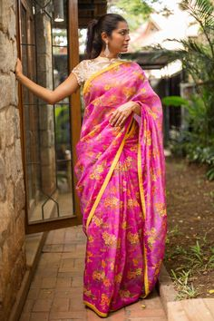 Beautiful zari worked flowers on a beautiful drape! A vivid pink saree with allover orange yellow green flowers. Sheer loveliness.A yellow blouse, and orange blouse, a green blouse or even a pink blouse. Pair away! #floral #pink #zari #saree #India #blouse #houseofblouse