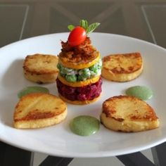 A multi-layered vegetable stack with grilled polenta and creamy herb sauce