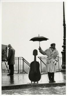 A man on the sidewalk in rainy Paris. The man uses his umbrella to protect his cello case. This is the famous cellist Maurice Baquet. The image was taken by photographer Robert Doisneau in 1957.