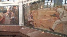 useliuksen mausoleumin Tuonelan joella -freskon reunassa on omakuva taiteilijasta, jolla on kädessä muurauslasta. Kuva: Kati Rantala / Yle  ---Taulu, jossa rakennetaan hirsitaloa.