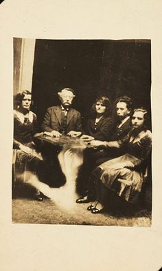 Spirit photography by paranormal investigator William Hope (1863–1933), who used multiple exposure techniques to render the appearance of ghost. Although his deception was exposed in 1922, he continued to dabble in the dark arts. A photograph of a group gathered at a seance. The information accompanying the spirit album states that the table is levitating – in reality the image of a ghostly arm has been superimposed over the table stand through double exposure.