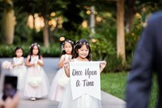 "Adorable flower girl with a ""Once Upon A Time"" sign"