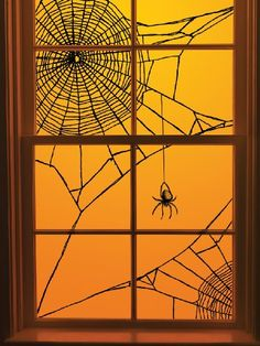 DIY Halloween Spiderweb Window Decoration ~ It's just black yarn, scotch tape... brilliant idea.