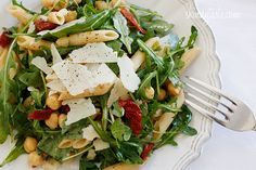 Arugula Salad with Penne, Garbanzo Beans and Sun Dried Tomatoes Recipe Salads, Main Dishes with baby arugula, penne pasta, sun-dried tomatoes, extra-virgin olive oil, balsamic vinegar, salt, ground pepper, garbanzo beans, parmigiano reggiano cheese