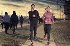 Active young couple jogging on a harbor promenade - Active young couple jogging side by side on a harbor promenade at sunset during their daily workout in a health and fitness concept
