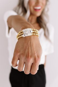 "The ""Kendley"" is a stretch bracelet with gold beads and block letter beads that spell the word ""mama!"" Each bracelet sold separately."