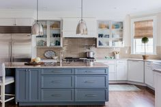 The slate blue island delivers a welcome dose of color to this pretty kitchen which also features an interesting mix of textures: stainless steel, woven shades, ceramic tile and a hardwood floor.