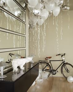 """Mirrored Wall  Mirrors cover one whole living room wall above and below the sideboard. """"Not only do the mirrors reflect the river, """"Kevin says, """"but they transform the view into art.""""  The balloons are not a permanent fixture. Kevin ordered them for a festive housewarming party."""