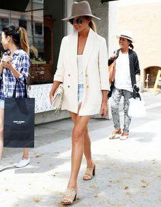 Street style Chrissy Teigen com shorts e blazer, no verão.