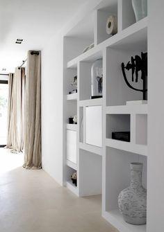 Etagères intégrées et longs rideaux de lin pour cet intérieur épuré.