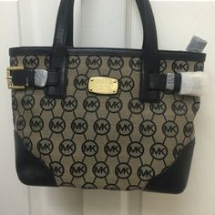 Authentic Michael knot purse NWT.  This handbag is made of uniquely designed fabric and trimmed with fine natural black leather.  This handbag has 4 open pockets inside and 1 with zipper, outside has 1 pocket. Zipper on the opening for closure Michael Kors Bags