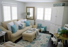 Beautiful, calm beach cottage living room, full of soft mushroom, blue, and white.  Painted furniture is so appropriate, and I love the cabinet, obviously holding a TV.