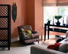 """Créez une ambiance """"amis de la terre"""" avec de chaudes teintes terreuses. L'assocation du terracotta chaleureux des murs et des meubles rouille et sable crée une atmosphère chaleureuse et lumineuse dans ce salon."""