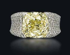 DIAMOND RING, Set with a fancy intense yellow cushion-shaped diamond, weighing approximately 8.38 carats, in platinum