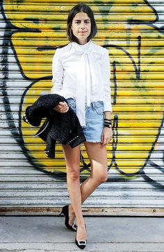 Leandra Medine wears a white pussybow blouse with cutoffs, a tweed jacket, and black pumps