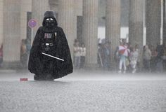 Berlin, Germany: A street performer in a Darth Vader costume waits to be photographed by tourists in front of the Brandenburg Gate during a thunderstorm