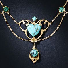 A rare and wonderful antique turquoise necklace - circa 1900 - created with classic Art Nouveau artistry. The centerpiece features a true blue turquoise heart set in a curvaceous golden frame that supports a free swinging turquoise centered drop dancing below. The swag necklace continues all around with twelve bezel set turquoises, all displaying black or brown spiderweb matrix.