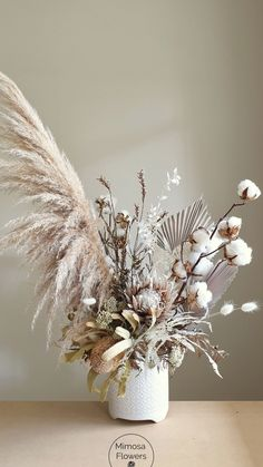 Dried flower arrangement in ceramic vessel with Pampas grass Palm spears cotton stems King Protea Banksia Bunny tails and more Banksia Pampas Cottonstems driedbouquet #