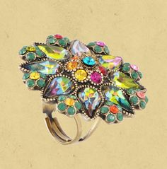 Michal Negrin ring with sparkling Swarovski crystals, beads and a painted flower. Adjustable band. The surface of the ring measures 1.5 inch in diameter.