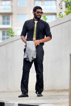 Gold hexagon tie on a full black outfit .